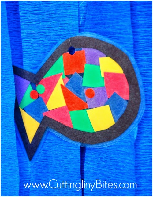 Rainbow Fish craft with blue ocean background, made for ocean theme week preschool