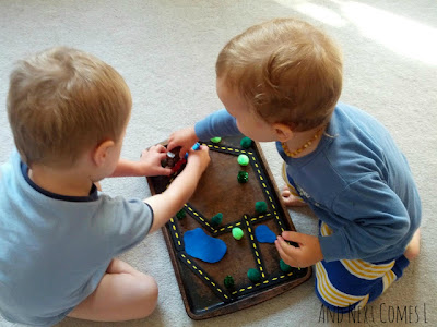 J and K playing with the magnetic roads busy bag from And Next Comes L
