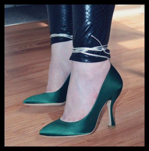 close up of feet in green satin shoes with silver ankle ties