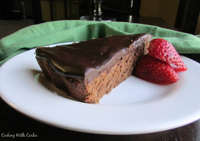 slice of chocolate topped sacher torte and fresh strawberries
