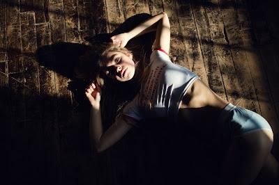 Linda chica rubia acostada en suelo de madera