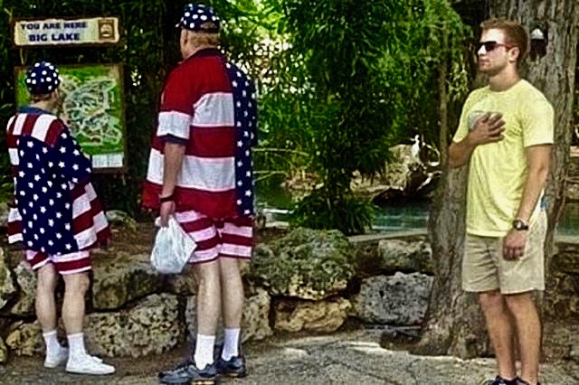 Patriotic overkill. A couple on tour of Big Lake in Americana shirts, shorts and hat. Young man from behind, hand over heart in flag pledge. The Smell of Freedom and other stories about 'merica. marchmatron.com