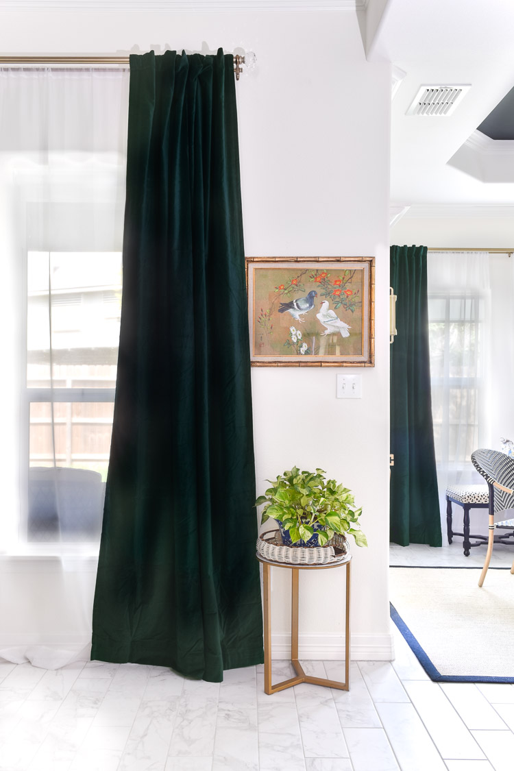Dark emerald green velvet curtains hanging in an open concept living and dining room area with black tray ceilings and white walls.