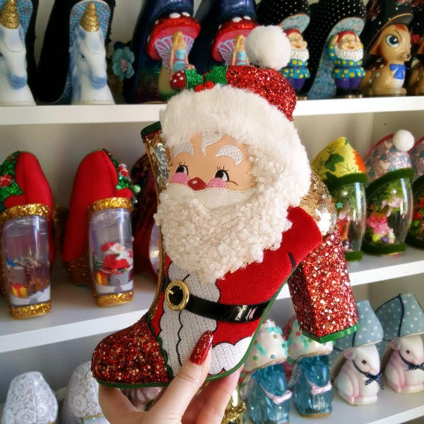hand holding red and gold festive themed ankle boot with Santa Claus applique face with shoe shelves in background