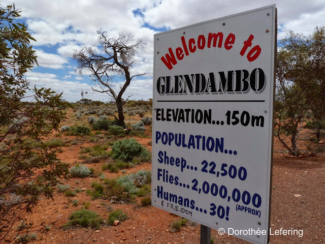 Street sign in a remote area of Australia. Welcome to Glendambo. 22,500 sheep. 2,000,000 flies. 30 humans.