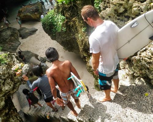 Tinuku Travel Surfing Uluwatu beach riding 8 meters Indian Ocean waves in hidden spots under sacred temple cliffs