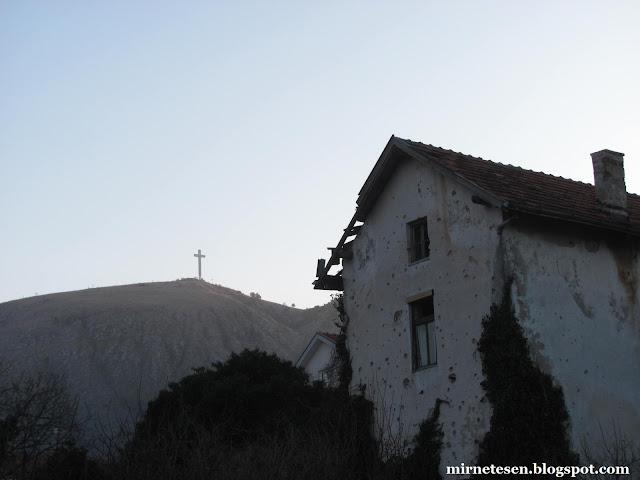 Мостар - крест на горе и дом, подвергшийся обстрелу