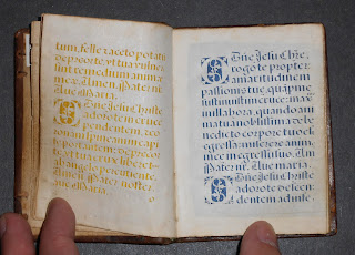 An open book of cut-out text, the lefthand side over yellow silk and the right hand over blue.
