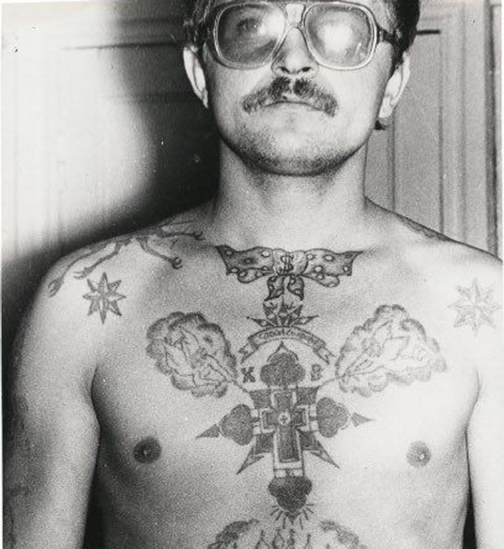 Text on the chest reads 'Save and protect.' Text on either side of the cross reads 'XV Hristos Voskres' (Christ has Risen). The eight-pointed stars on the clavicles denote a high-ranking thief. A bow tie tattooed on the neck is often found in strict regime colonies. Originally, bow ties were dishonourable tattoos. They were forcibly applied underneath the clavicle cat tattoos of pickpockets who had broken the 'thieves' code' and sided with the authorities. Today, however, there is no stigma attached to them. The dollar sign on the bow tie shows the bearer is either a safecracker, money launderer or has been convicted for the theft of state property.