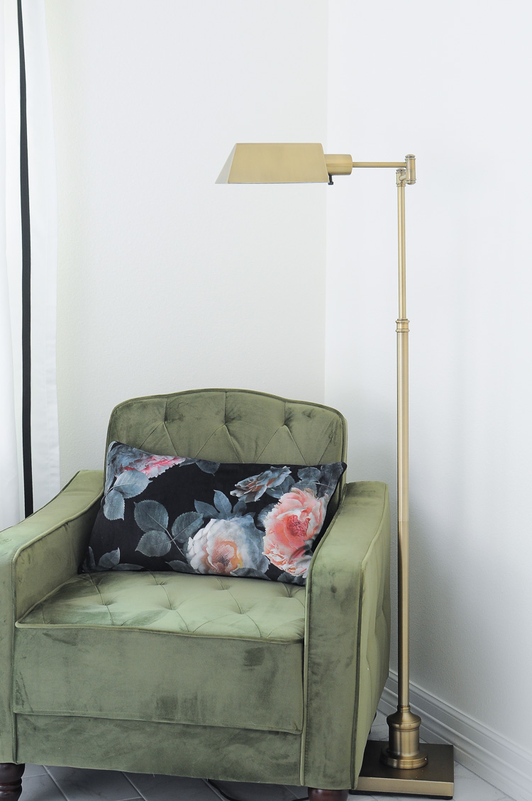 Aged brass pharmacy reading floor lamp next to a gorgeous green tufted chair in a glam and chic master bedroom.