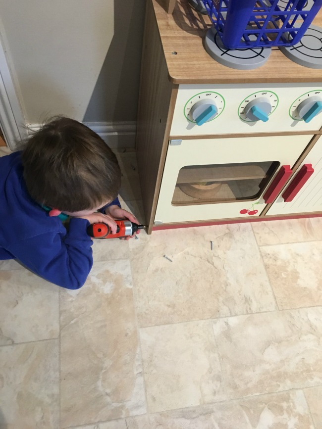 boy-using-a-screwdriver-to-take-screws-from-a-wooden-toy-kitchen