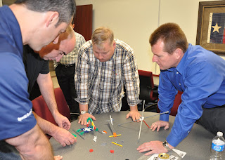 Law enforcement officers test the dirty dozen of human error in a timed exercise building a model helicopter.