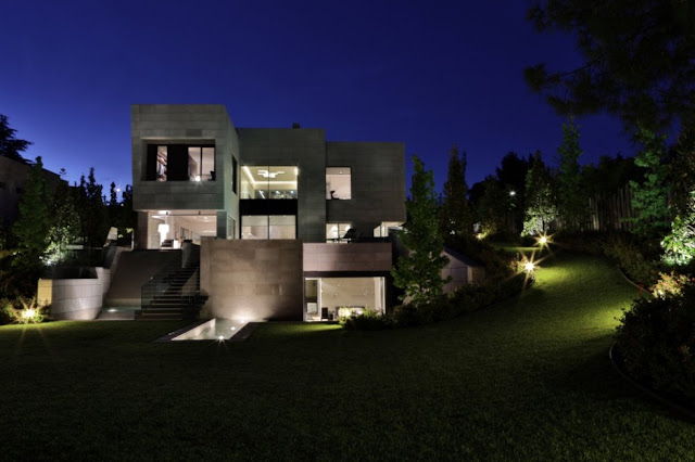 The Memory House by A-Cero Architects at night from the backyard