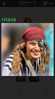 Пират с перевязанным глазом улыбается с повязкой на голове