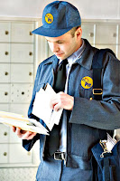 Posta kutuları önünde duran postacı