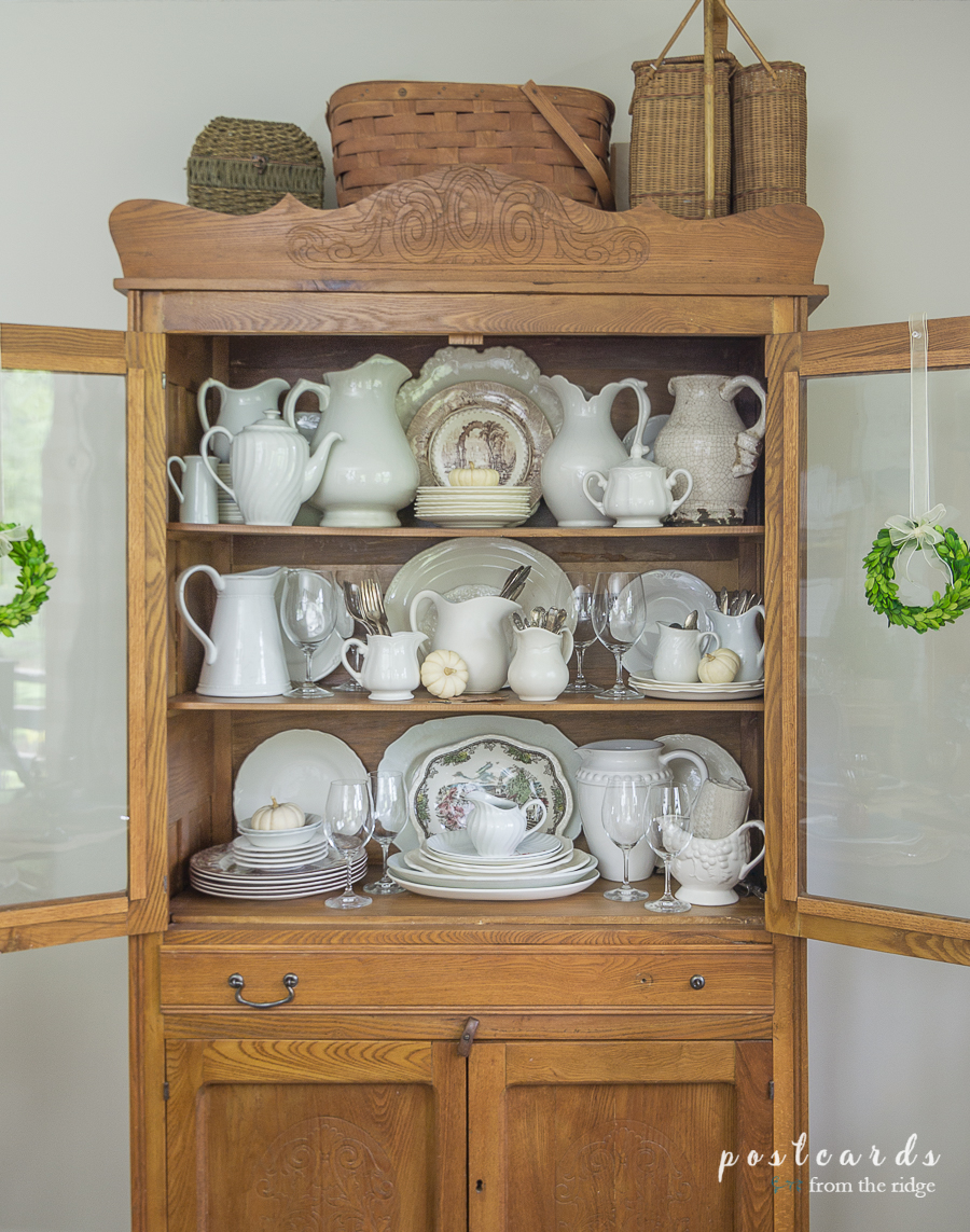 white dishes in farmhouse oak hutch