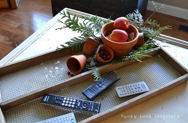 Christmas vignette with apples, evergreen branches inside plant pots on an antique soil sifter. Perfect for tv remotes!
