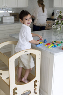 A kid is standing on an enclosed kitchen stool to help in the kitchen.