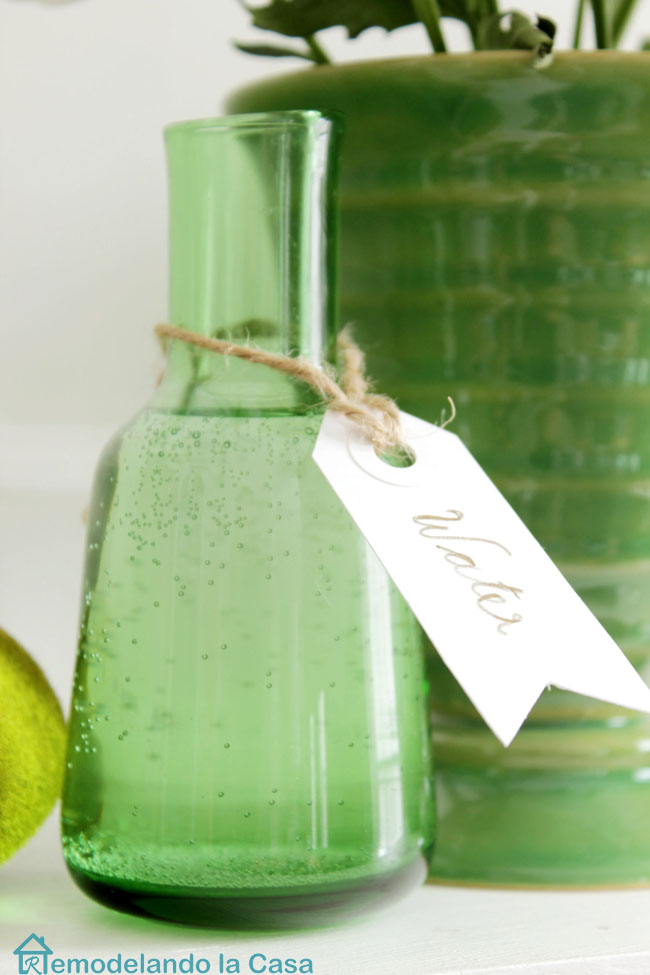 little green glass bottle of water with tag on mantel