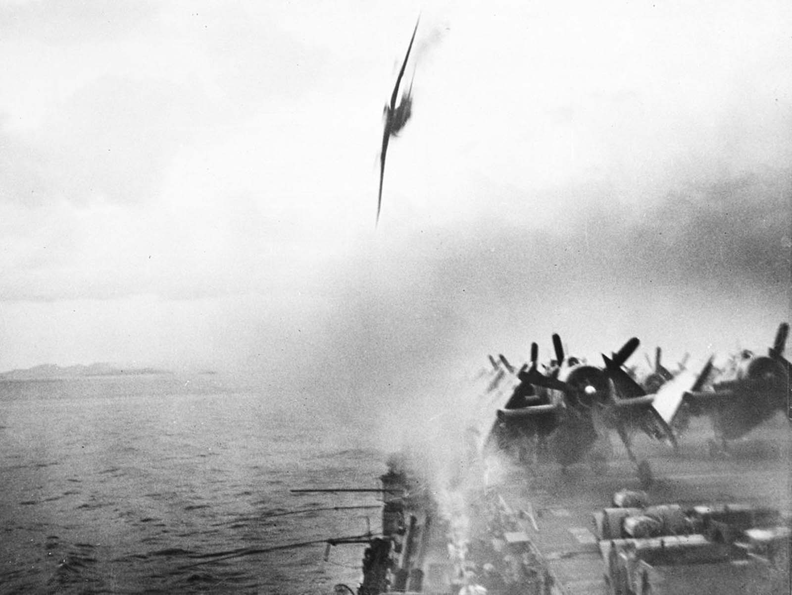 Anti-aircraft gunners, center foreground, pour a deadly stream of fire into an already-burning Japanese Kamikaze plane plummeting toward the flight deck of the USS Sangamon, a Navy escort carrier, during action in the Ryukyu Islands near Japan, on May 4, 1945. This suicide plane landed in the sea close to the carrier. Another Japanese aircraft later succeeded in hitting the ship deck, inflicting heavy damage.