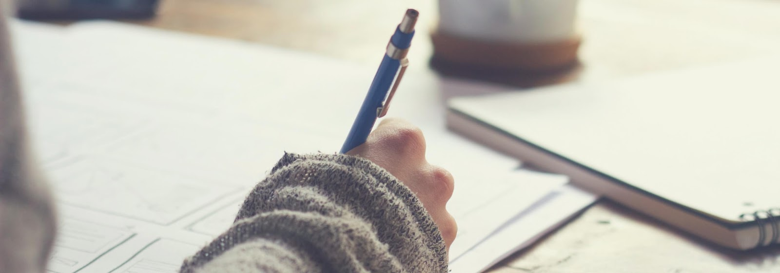 A woman's hand holds a pen to a pile of papers on a desk. A coffee cup and a notebook is blurred in the background.
