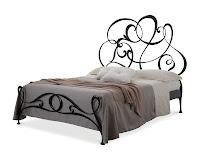 Baş tarafında metalden dalgalı desenler olan yatak odası karyolası