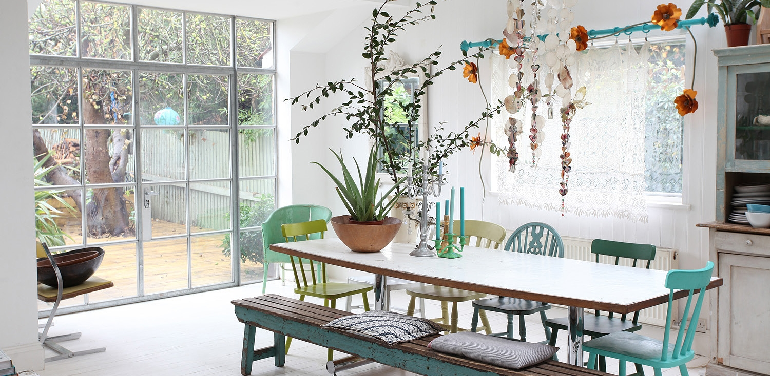 bohemian interior dining room with assorted chairs, houseplants, white floors and rustic furniture