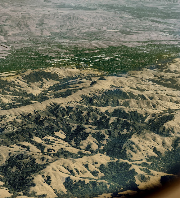 An aerial photo taken somewhere over the US - notice the sandy coloured mountains and small bits of greenspace?