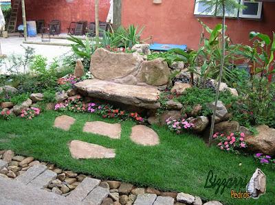 Pisadeira de pedra no jardim, com pedra moledo tipo chapada, com tamanhos variados, de 40 cm a 70 cm.