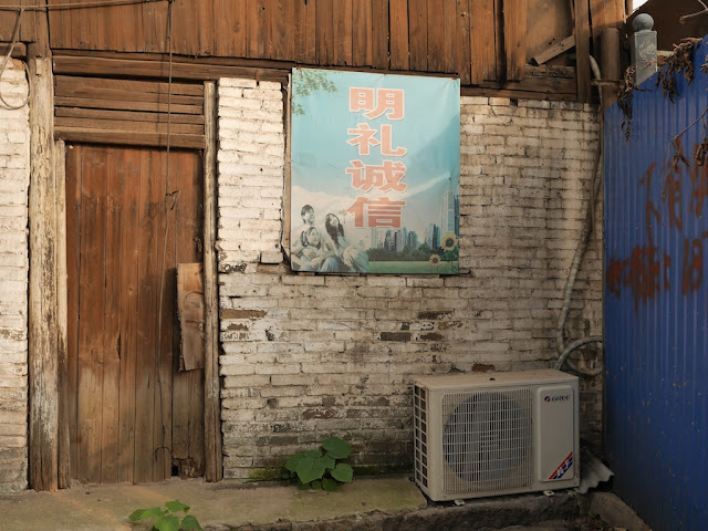 """明礼诚信"" sign on a brick wall"
