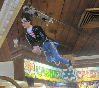 Papiere mache figure of Harry Potter on a broom, flying on wires near the ceiling