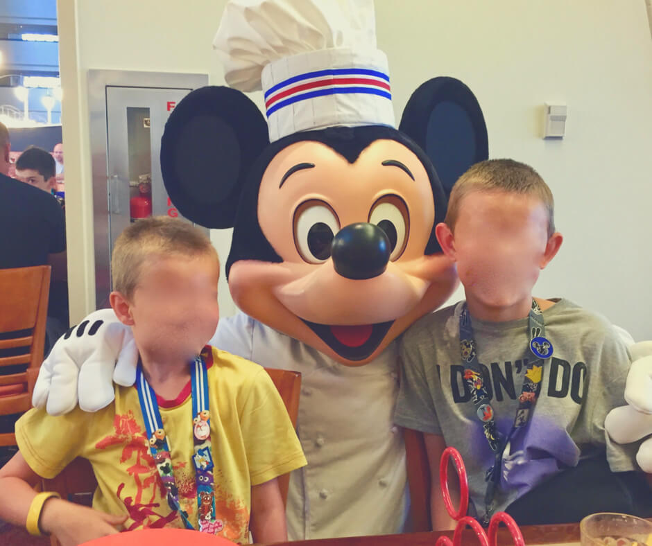 Mickey Mouse with his hands on two boys' shoulders, in a restaurant