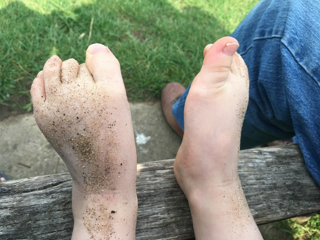 toddlers-feet-covered-in-sand