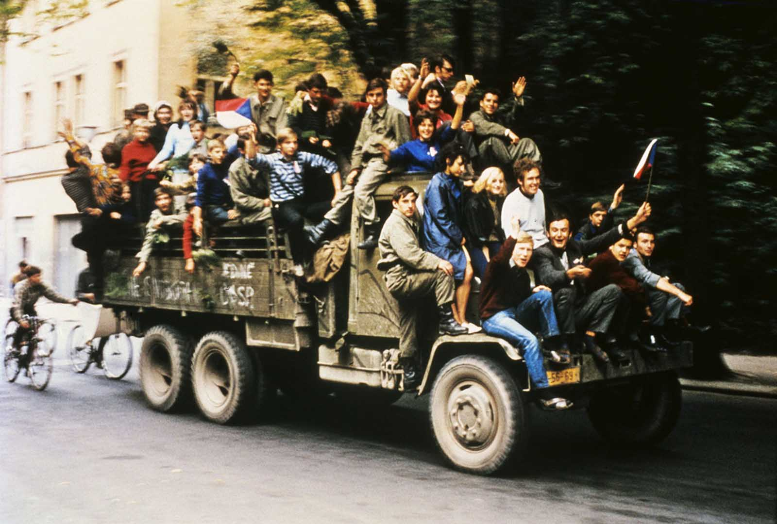 Czechoslovakian army trucks take young people around Prague as Soviet tanks had halted on the outskirts of town and began a siege of Czech army barracks. The passengers waved Czechoslovakian national flags and chanted national songs and patriotic slogans.
