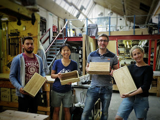 Image of people holding wooden boxes in a workshop