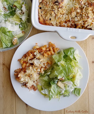 dinner plate loaded with chicken pasta casserole and salad with remaining salad and casserole nearby