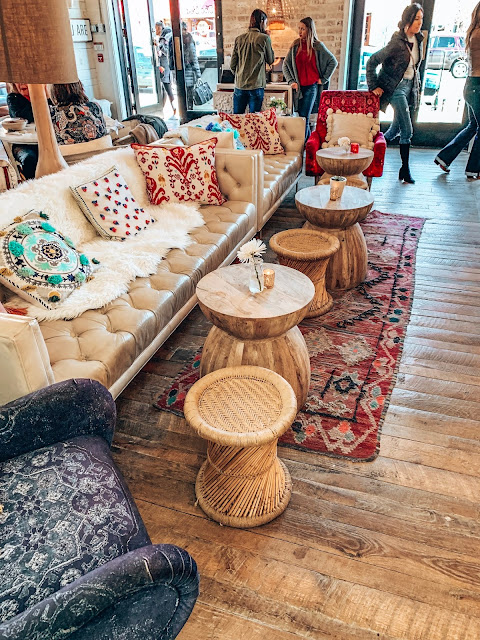 Boho seaitng are a the bar with white faux fur throws, wooden tables and a red Moroccan rug