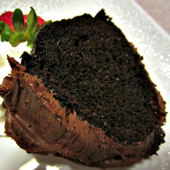 Easy Mexican Chocolate Cake by Renee's Kitchen Adventures slice on a white plate garnished with whipped cream and a strawberry