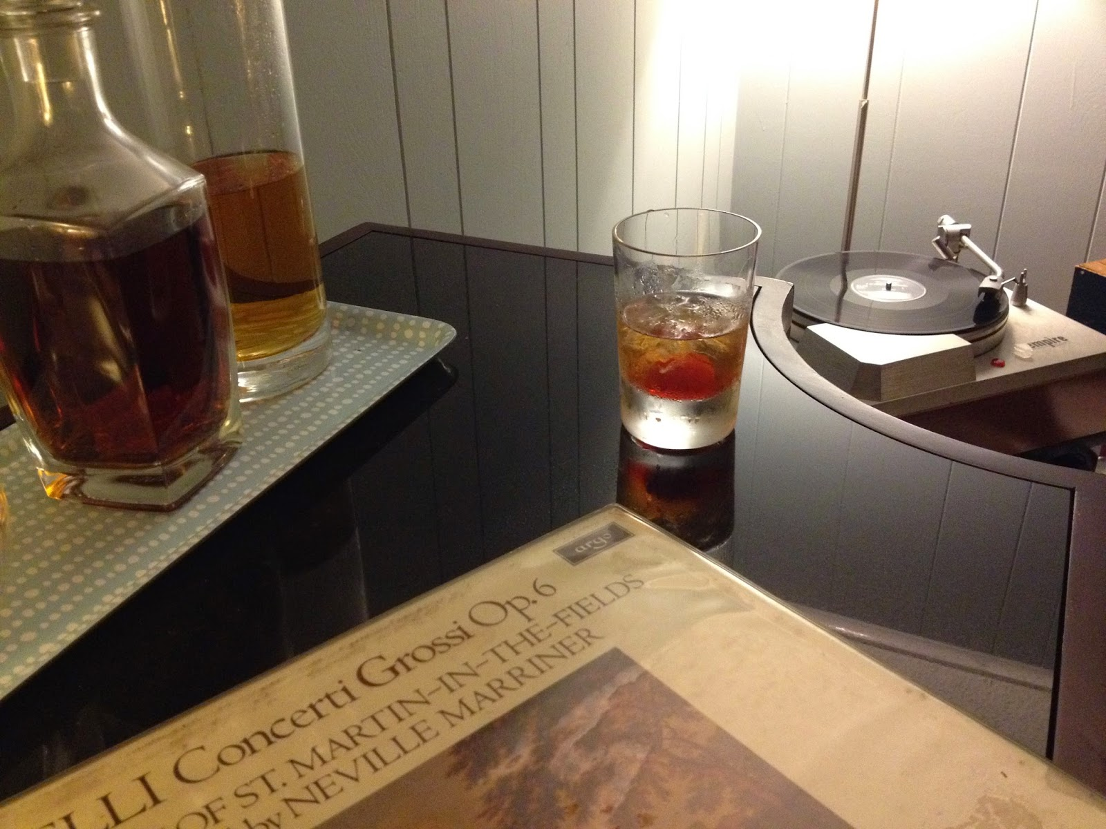 an Old Fashioned cocktail with decanters of bourbon and scotch.