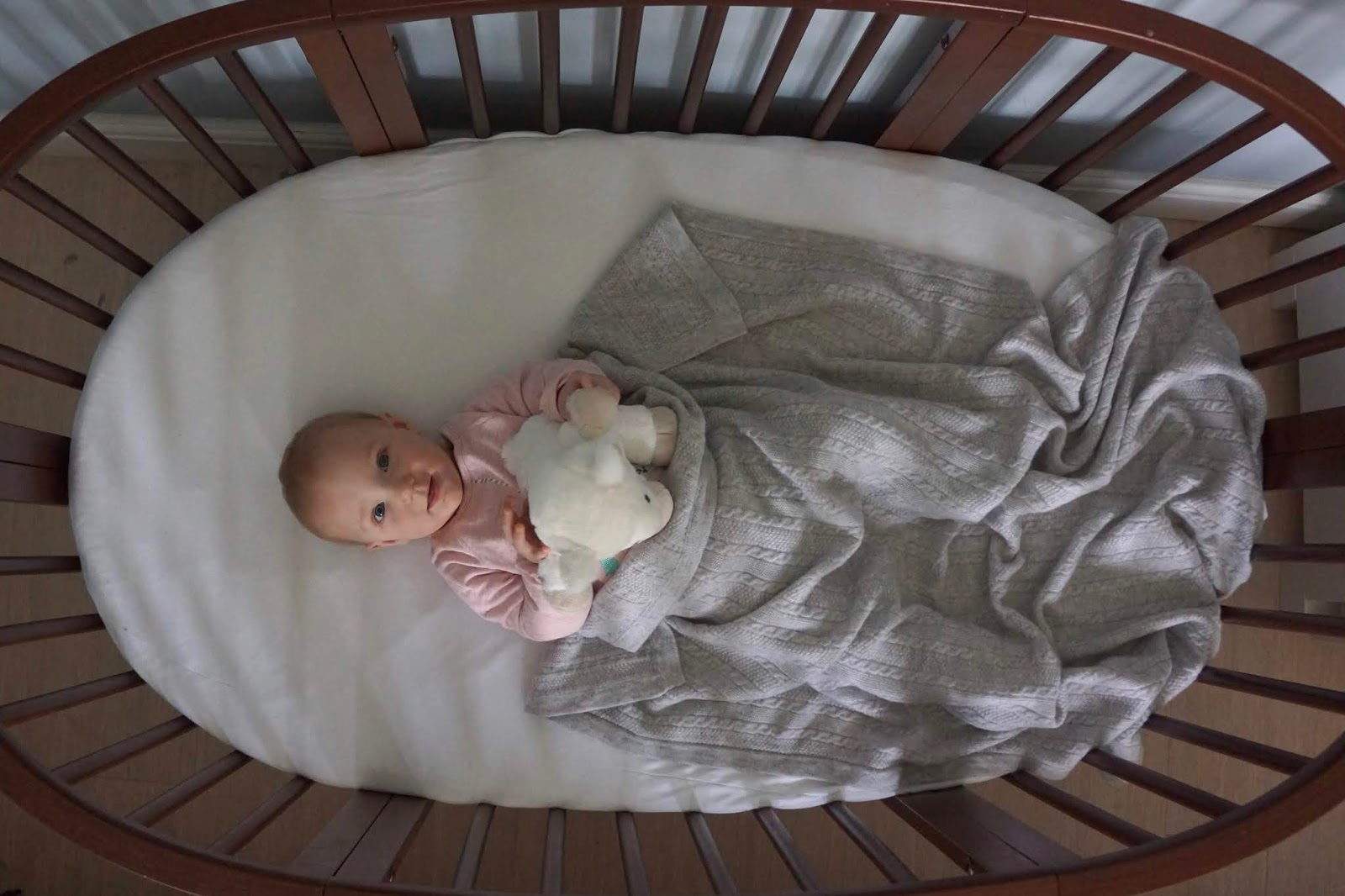 baby in a cot with grey blanket