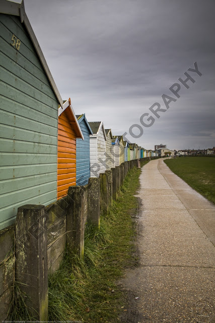 Colourful beach huts on a sweeping curve overlooking the grass