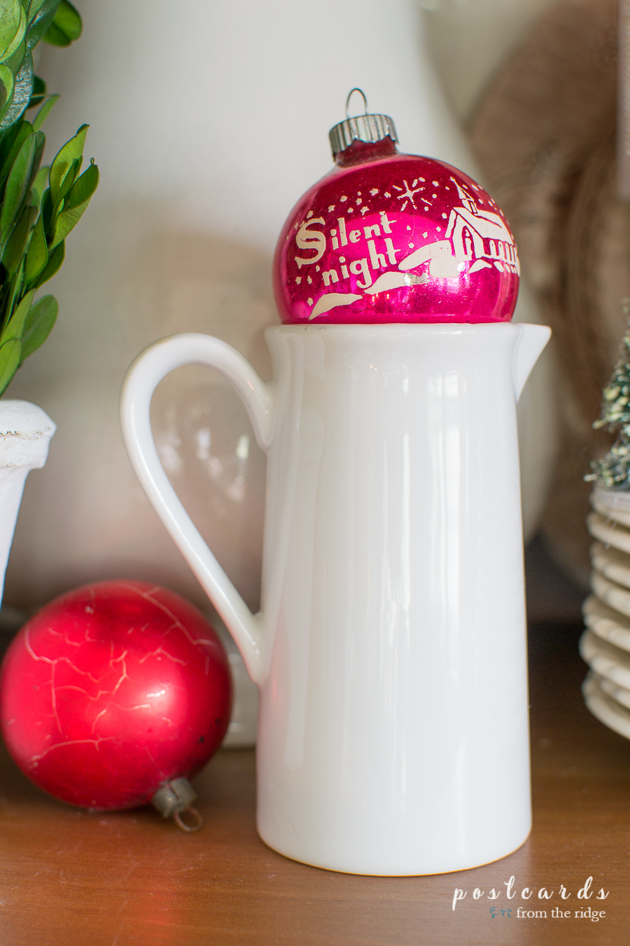 little white creamer and vintage Christmas ornaments