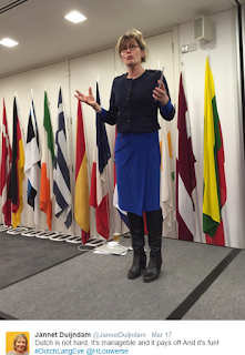 Pic of Henriette Louwerse teaching on stage with wide range of European flags behind here