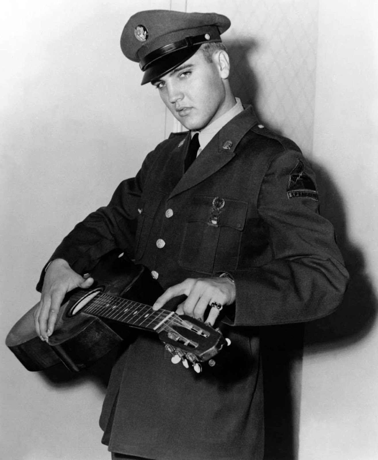 Presley the soldier poses with his guitar.