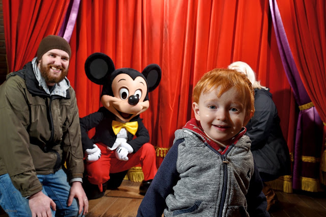 Smiling redhead boy close up to the camera, with a Mum and Dad and Mickey Mouse in the background