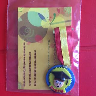 medalla en fondo azul y amarillo en el que se muestra la figura de un niño con birrete y el nombre de Rubén. Todo en fimo. Cinta con los colores de España: rojo y amarillo