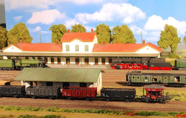 Diverse treinen rijden Station Gennep binnen. Enkele goederenwagons staan op de opstelsporen.