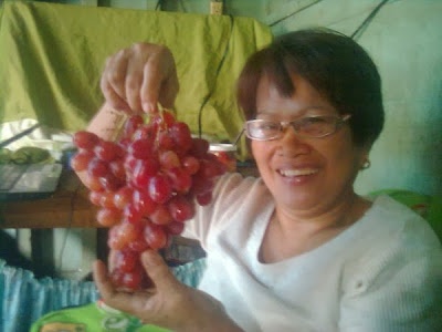My wife displaying a bunch of grapes