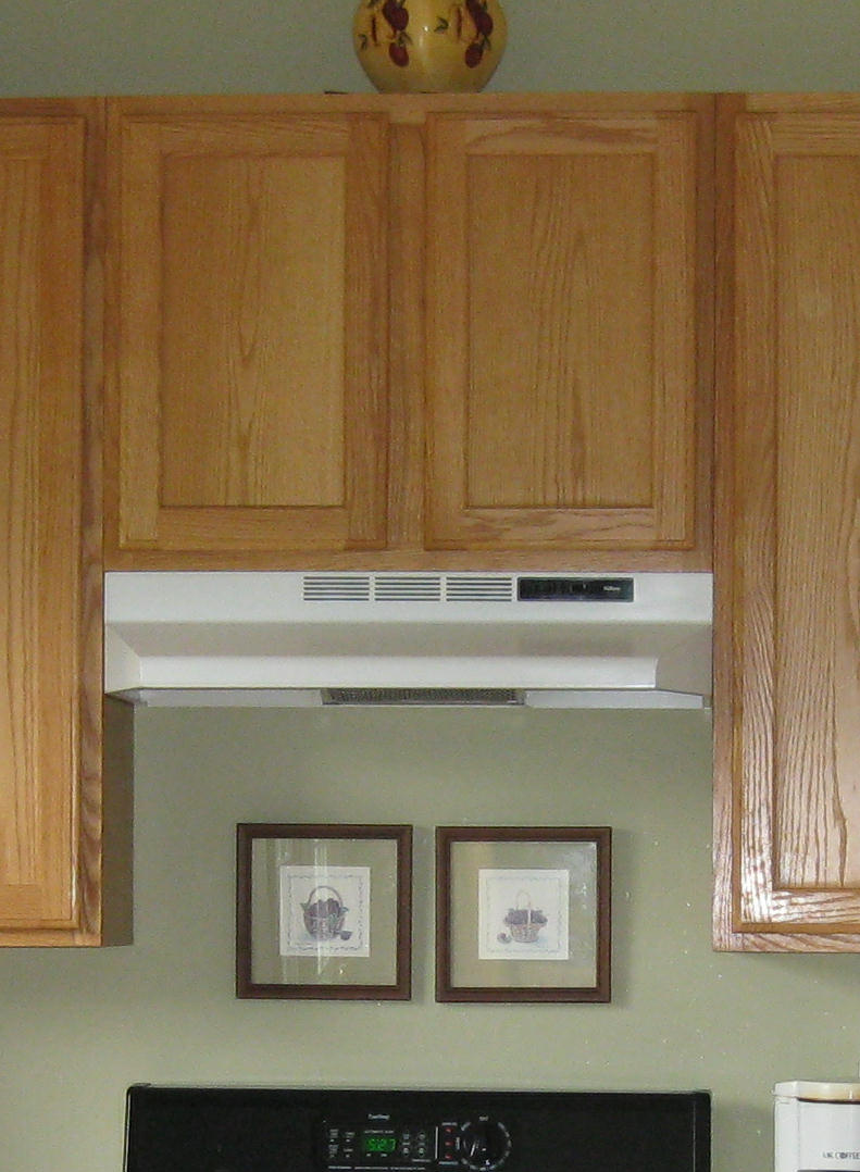 Dated Kitchen With Oak Cabinets And Recirculating Fan