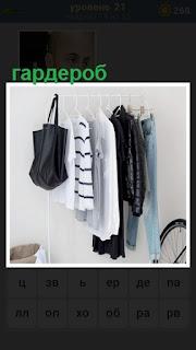 небольшой гардероб устроен в комнате, вешалка и висит одежда